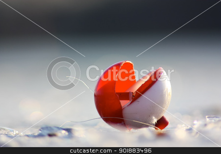 Broken Bobber stock photo, A broken fishing bobber on the Winter ice. by Ken Wolter