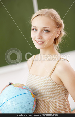 Teacher at school with a globe stock photo, Young female teacher holding a globe at school by Sergey Nivens