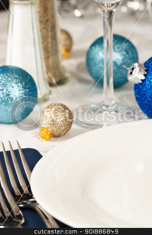 Festive Holiday Table Setting stock photo, Christmas ornaments in blues and gold decorate a festive holiday table with an empty white plate providing copy space by Karen Sarraga