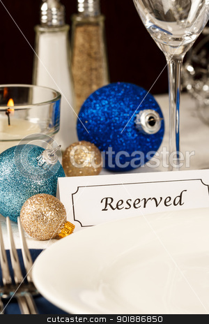 Decorated Holiday Table Setting stock photo, A holiday table setting with an empty plate providing copy space is decorated with blue and gold ornaments and a placard showing a reserved place by Karen Sarraga