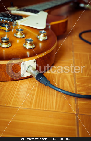 electric guitar on floor with cable stock photo, Electric guitar honey burst color on floor with jack cable by moggara12