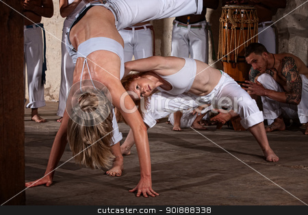 Woman Dodges Capoeria Kick stock photo, Woman leans in to dodge her attackers foot in Capoeira by Scott Griessel
