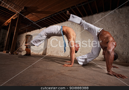 Two Capoeria Performers Fighting stock photo, Two strong male capoeira experts fighting indoors by Scott Griessel