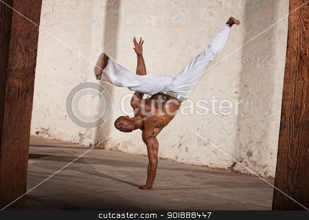 Attractive Man Kicking stock photo, Attractive Brazilian man performing a capoeria kick by Scott Griessel