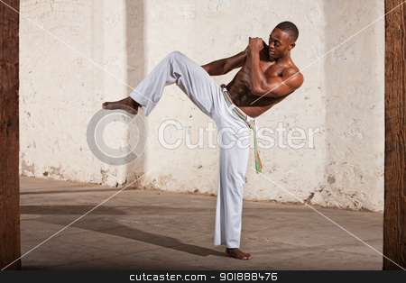 Capoeria Knee Kick Demonstration stock photo, Young Black man demonstrating a knee kick indoors by Scott Griessel