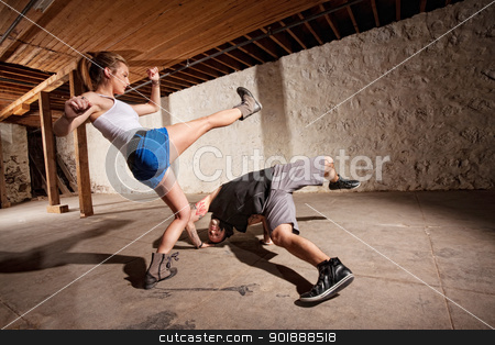 Capoeria Experts Kicking and Dodging stock photo, Male and female capoeria sparring partners working out by Scott Griessel