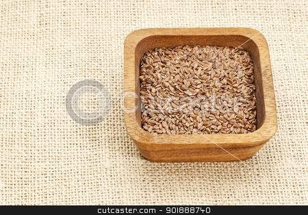 brown flax seeds stock photo, brown flax seeds in square wooden bowl against burlap canvas by Marek Uliasz