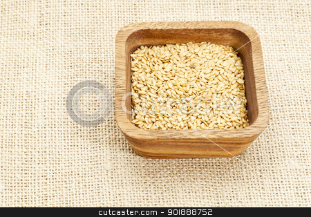 gold flax seeds  stock photo, gold flax seeds in square wooden bowl against burlap canvas by Marek Uliasz