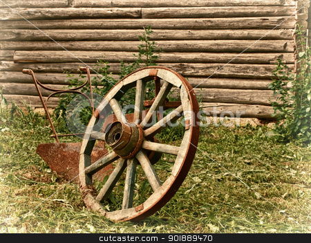 village theme stock photo, wheel and plough on the grass near the wooden wall by Sergej Razvodovskij