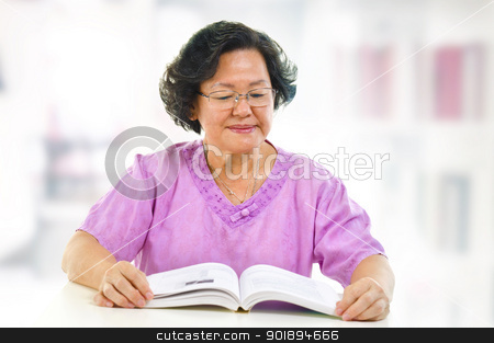 Home reading stock photo, Asian senior woman serious reading book at home by szefei
