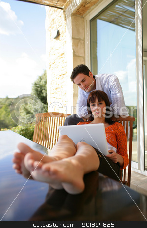 Couple using laptop on their patio stock photo, Couple using laptop on their patio by photography33