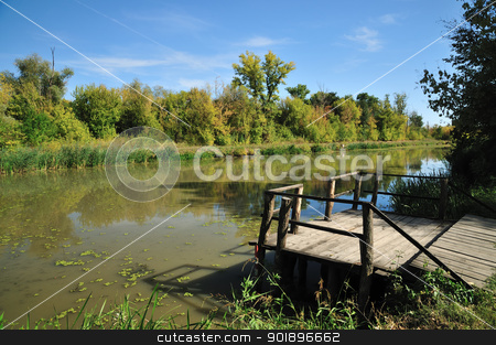 Autumn by river stock photo, Early autumn sunny day by river with colorful trees reflection on water by zagart