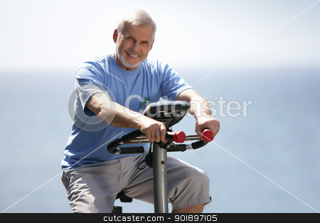 Senior man using an exercise bike outdoors stock photo, Senior man using an exercise bike outdoors by photography33