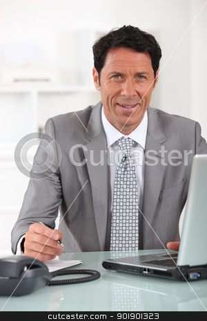 Businessman sitting at his desk with a laptop computer stock photo, Businessman sitting at his desk with a laptop computer by photography33