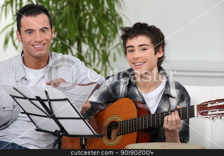 Adolescent boy learning to play the guitar stock photo, Adolescent boy learning to play the guitar by photography33