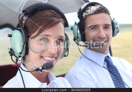 Man and woman wearing headsets in the open cockpit of a light aircraft stock photo, Man and woman wearing headsets in the open cockpit of a light aircraft by photography33