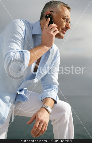 Man admiring the coastal view whilst making a telephone call stock photo, Man admiring the coastal view whilst making a telephone call by photography33