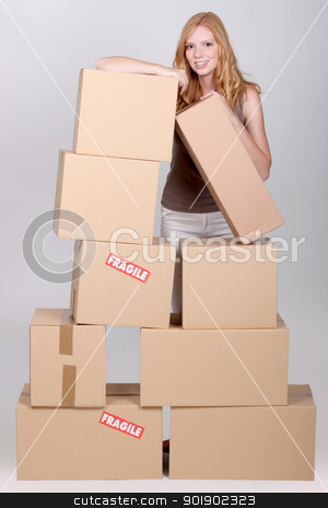 Young woman surrounded by cardboard boxes stock photo, Young woman surrounded by cardboard boxes by photography33