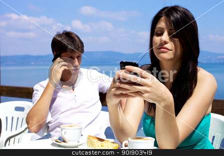 Beautiful woman smiling while texting on cellphone stock photo, Woman texting man talking on cellphone during breakfast on a lake by federico marsicano