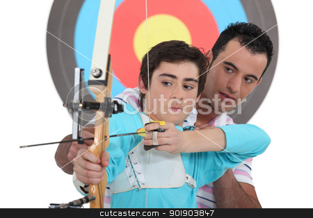Boy having archery lesson stock photo, Boy having archery lesson by photography33