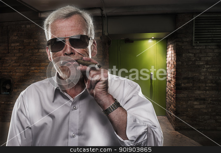 Retired man with strong personality stock photo, Retired man with strong personality standing in the darkness in sunglasses puffing on a big cigar, quintessential stereotype of a retired successful executive by Instudio 68