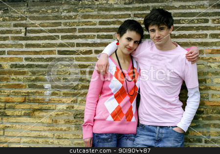 Boy and girl leaning against a wall stock photo, Boy and girl leaning against a wall by photography33