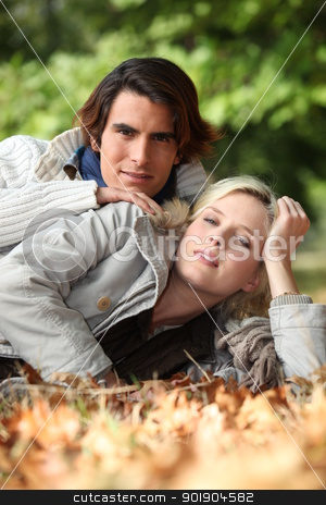 Young couple laying in autumnal leaves stock photo, Young couple laying in autumnal leaves by photography33