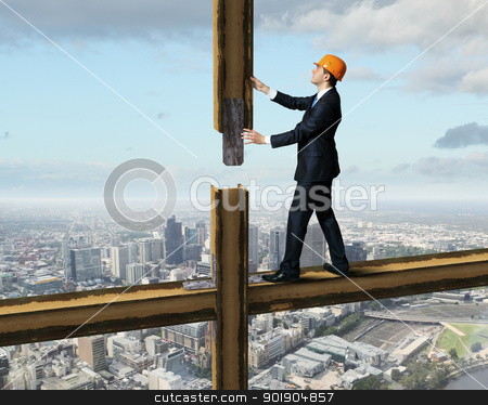 Businessman standing on the construction site stock photo, Businessman standing in suit on the construction site by Sergey Nivens