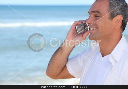Smiling man using a cellphone by the ocean stock photo, Smiling man using a cellphone by the ocean by photography33