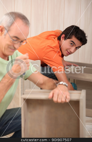 Grandfather with grandson assembling furniture stock photo, Grandfather with grandson assembling furniture by photography33