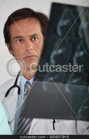 Doctor looking at X-ray stock photo, Doctor looking at X-ray by photography33