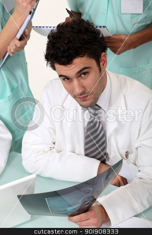Three hospital workers gathered around x-ray image stock photo, Three hospital workers gathered around x-ray image by photography33