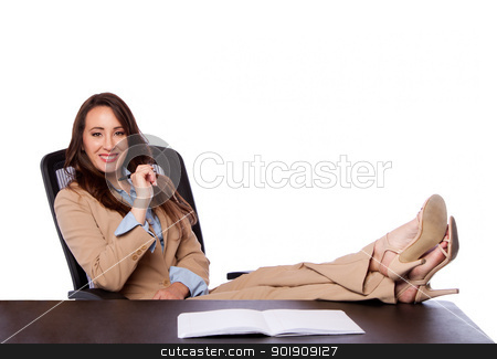 Corporate business woman at desk stock photo, Beautiful attractive happy corporate lawyer business woman sitting in office holding pen and feet on desk, isolated. by Paul Hakimata