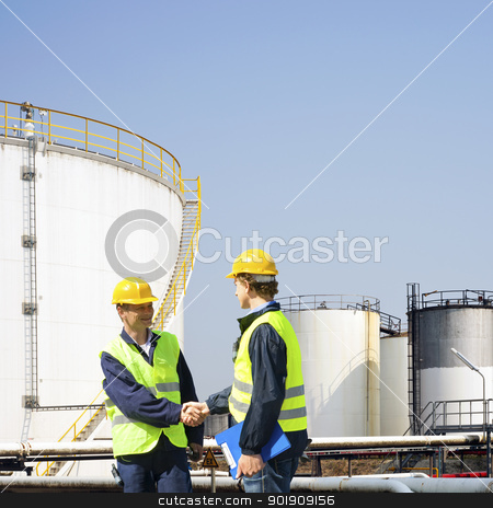 Oil industry stock photo, Two oil industry workers shaking hands in front of the storage tanks of a petrochemical refinary by Corepics VOF