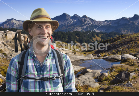 Smiling mountain guide stock photo, Smiling mountain guide with a backpack and walking stick on his back on a sunny afternoon in the middle of nowhere by Corepics VOF