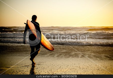 Surfer walking stock photo, Surfer walking on the beach with the waves at sunset in Portugal. by Homydesign 
