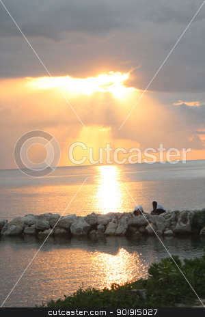 Sun setting through the clouds stock photo, The rays of the sun piercing through the clouds as it sets. by Billy Shell