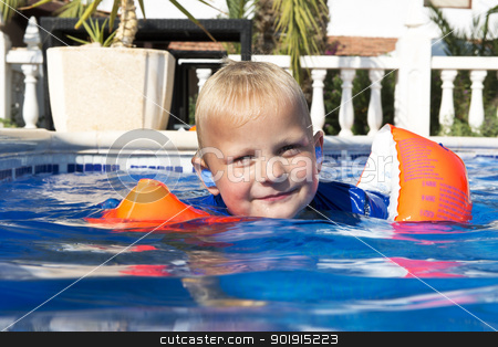 Learning to swim stock photo, Young boy wearing inflatible floating wings learning to swim in an outdoor pool by Corepics VOF