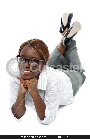 Relaxed african businesswoman lying on floor stock photo, Relaxed african businesswoman lying on floor. Indoor studio shot by Ishay Botbol