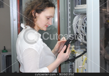 Woman working on telecommunication equipment stock photo, Woman working on technical site of mobile switching center for connection cellular phones by Aikon