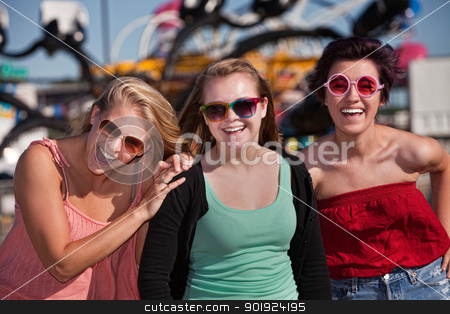 Three Cute Laughing Girls stock photo, Group of three laughing teenage girls at an amusement park by Scott Griessel