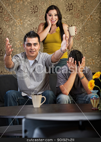 Excited Family Watching TV stock photo, Excited man and woman with distraught son watching television by Scott Griessel