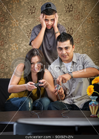 Hispanic Family stock photo, Embarrassed Hispanic teenager behind parents playing video games by Scott Griessel