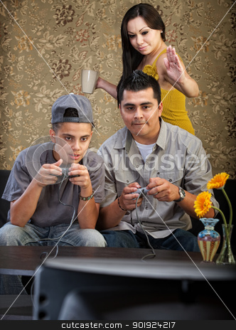 Funny Hispanic Family Playing Video Games stock photo, Mother vying for attention from husband and son playing video games by Scott Griessel
