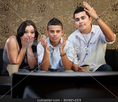 Shocked Hispanic Family Watching TV stock photo, Shocked family of three watching television with hands in the air by Scott Griessel