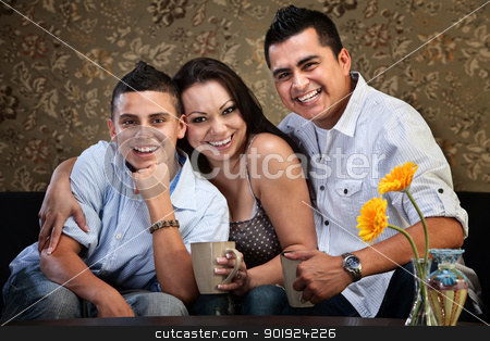 Young Happy Native American Family stock photo, Happy Latino family of three embracing on a sofa by Scott Griessel