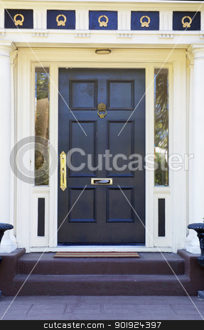 Colonial Black Door stock photo, Colonial style black door on white house with  gold ornamentation above by bobkeenan