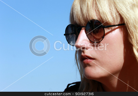 Female teenager in sunglasses stock photo, Portrait of thoughtful blond haired teenager in sunglasses, blue sky background. by Martin Crowdy