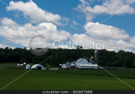rural farmstead stock photo, farm buildings and fields in a rural setting with buildings crops and a cloudy sky by digitalreflections