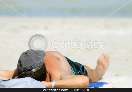 Man sunbathing on beach stock photo, Rear view of man sunbathing on sandy beach with sea in background. by Martin Crowdy